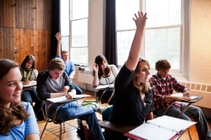 High school students in an old looking classroom raise their hands to answer a question.